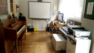 [Image of a music studio with a piano on the left, a Smart Board directly ahead, and a computer, keyboard, and printer/scanner to the right.]