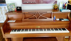 [Image of a LeSage upright piano in medium brown wood. There are ornaments from students, a sticker sheet, and flashcards on top of the piano.]