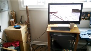 [Image of Kit Murley's instrument collection (including three ocarinas and a didgeridoo), flute, and all-in-one computer with tea mug sitting next to it.]