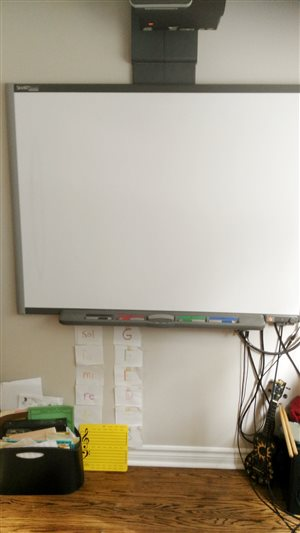 [Image of a Smart Board. Beneath it are music books and a series of pictures showing fixed do equivalents to the musical alphabet.]